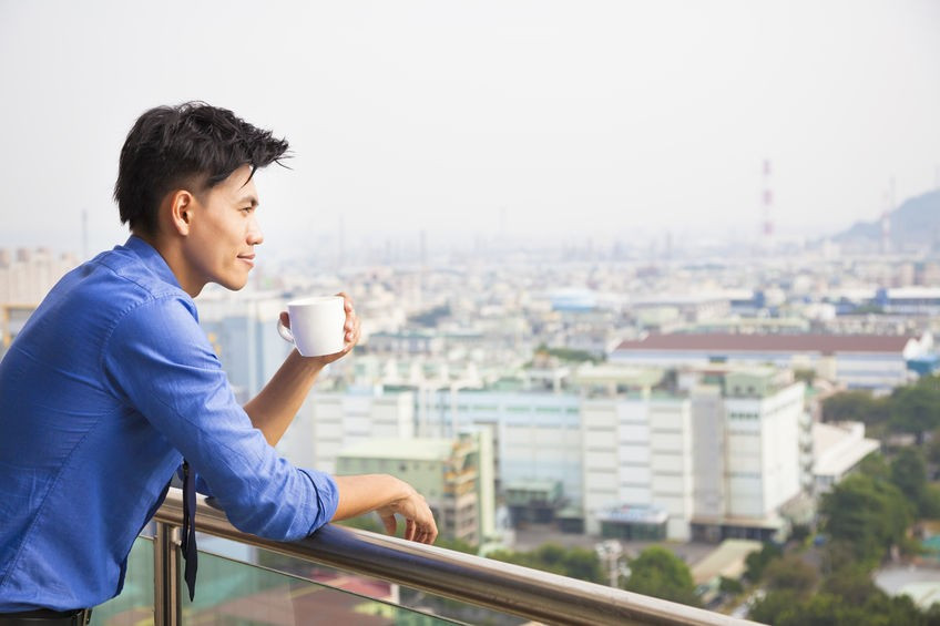 Man standing over a balcony drinking from a mug.