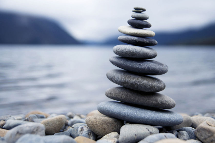 A teetering stack of stones with a sea in the background