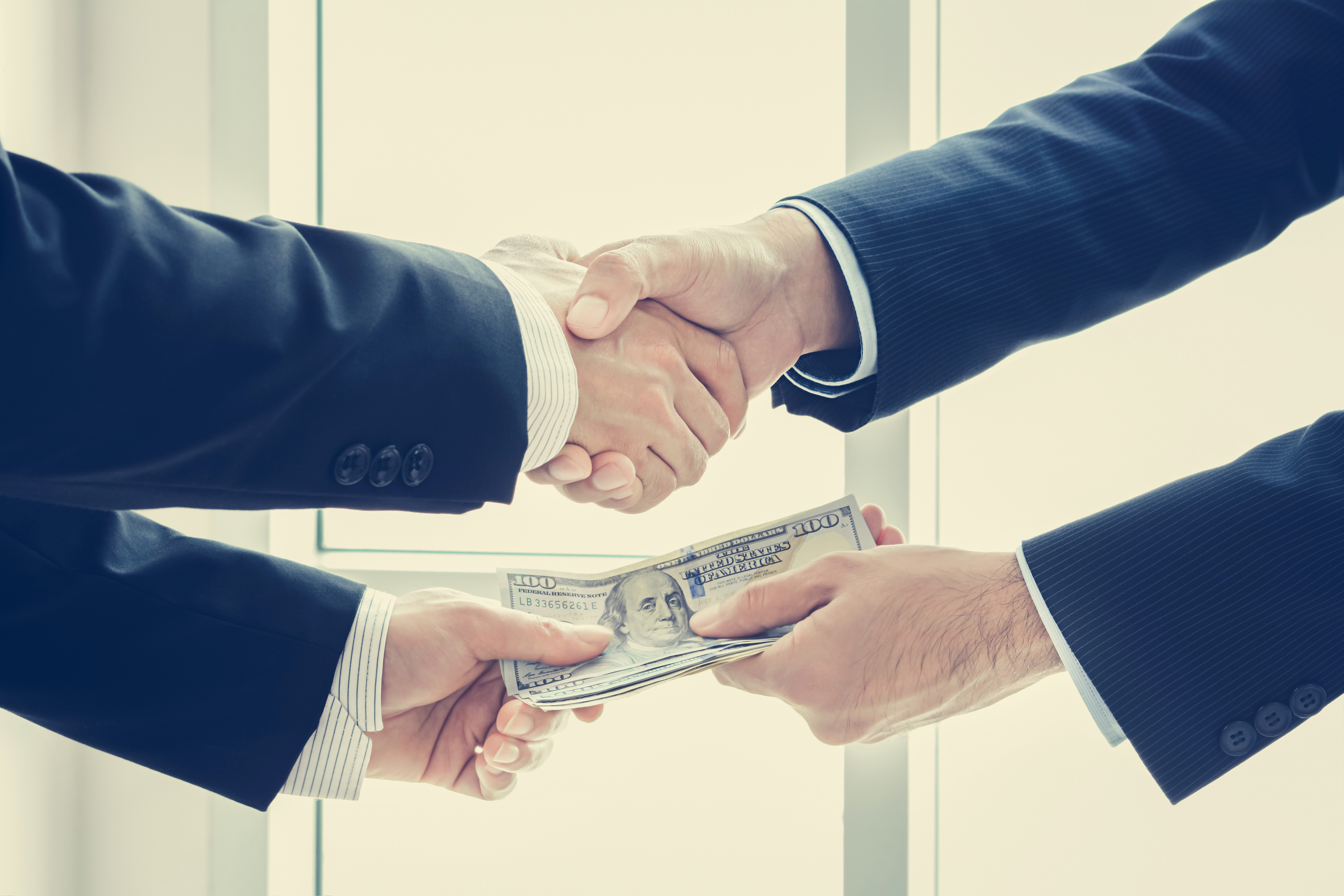Two hands shaking while exchanging a stack of money with the other hands