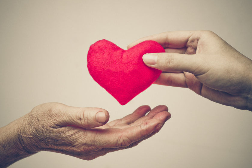 One hand giving a stuffed heart to another hand