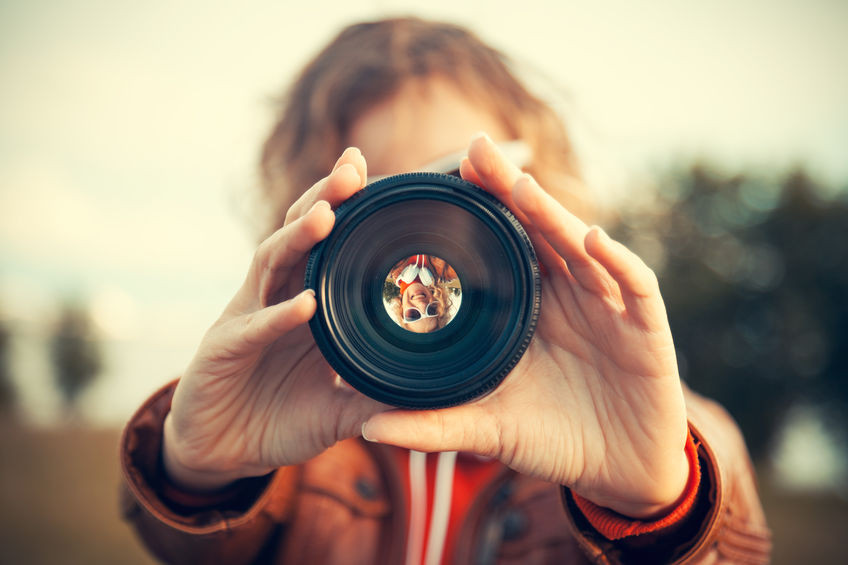 Person looking through a camera lens to focus.