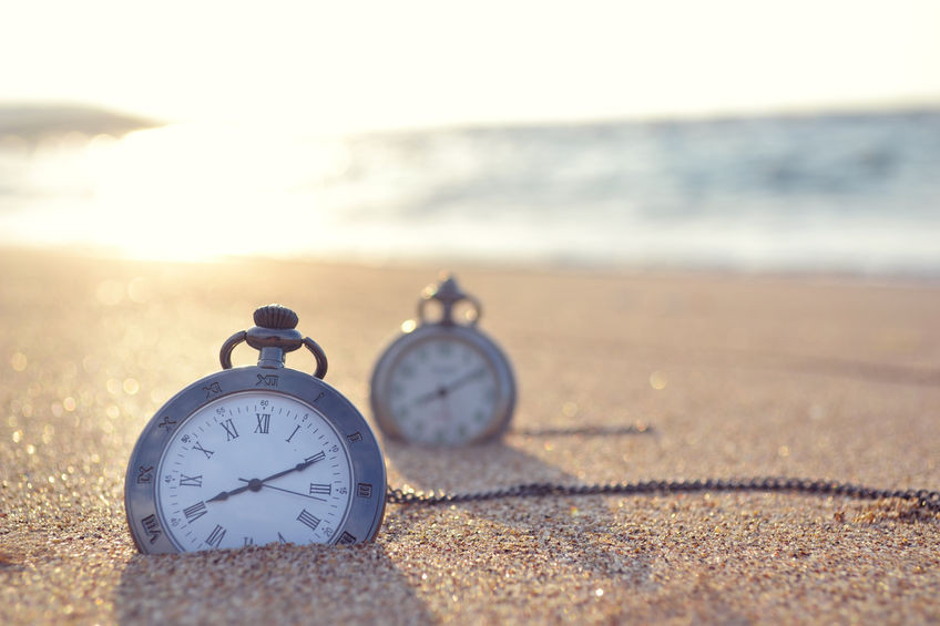 Two pocket watches in the sand on the beach