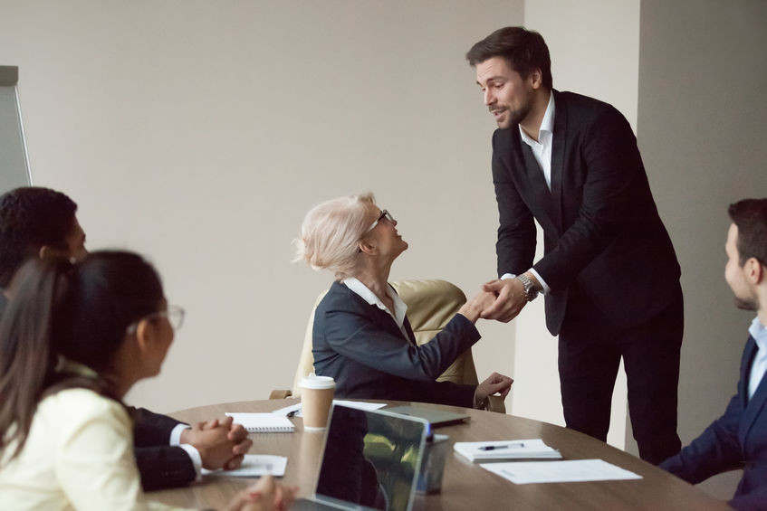 Man shaking hands with woman at head of a conference table