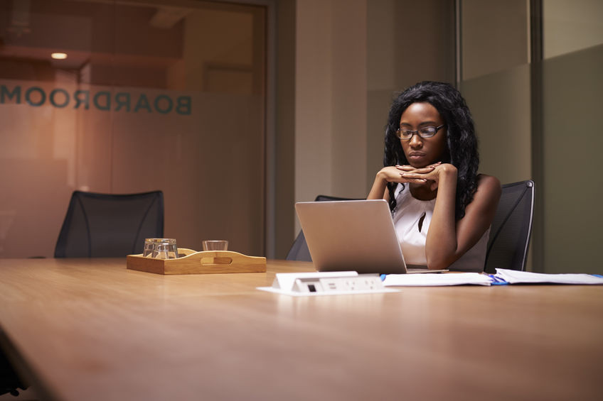 Woman sitting in a conference room staring at laptop