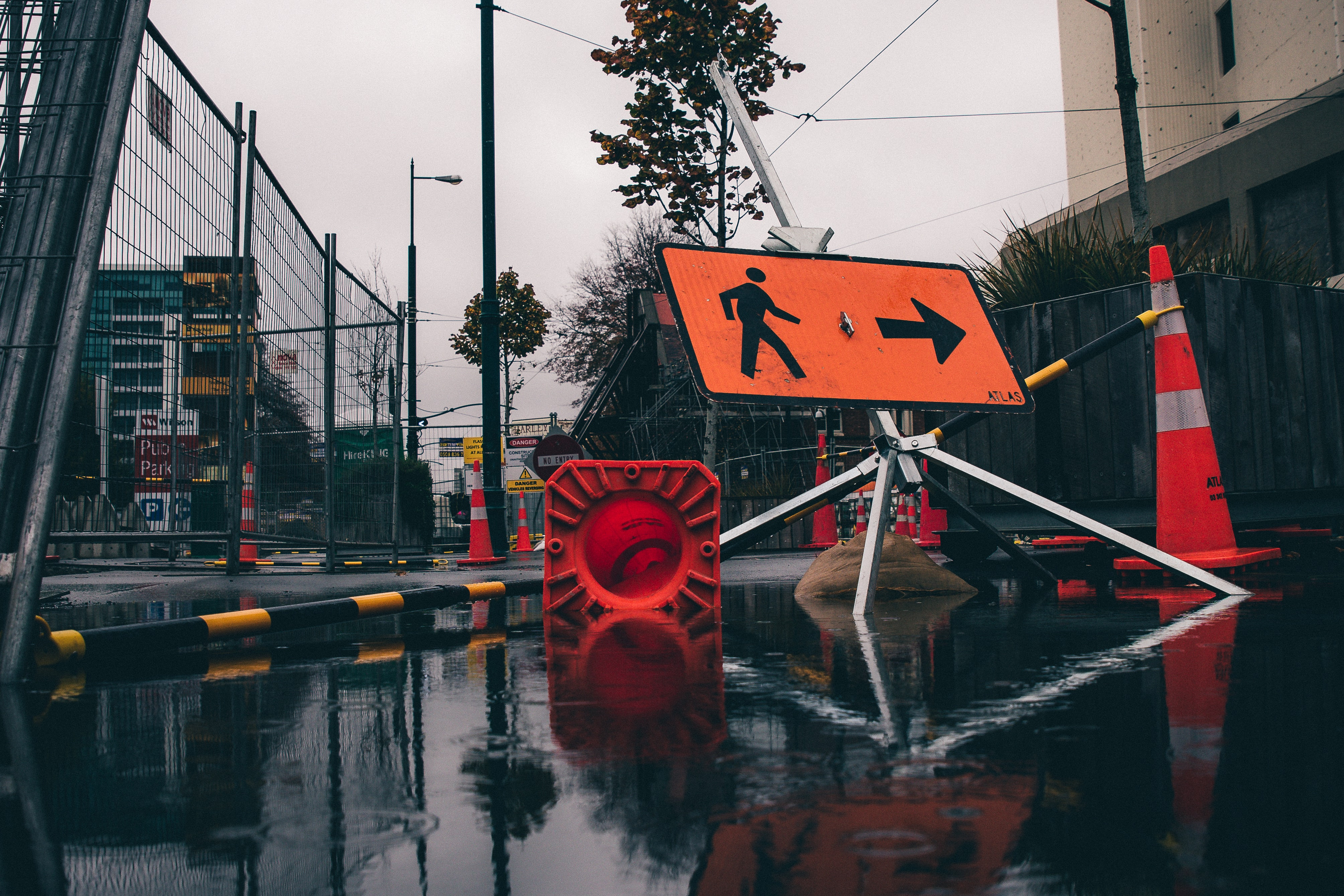 a city street partially flooded with a detour sign for pedestrians