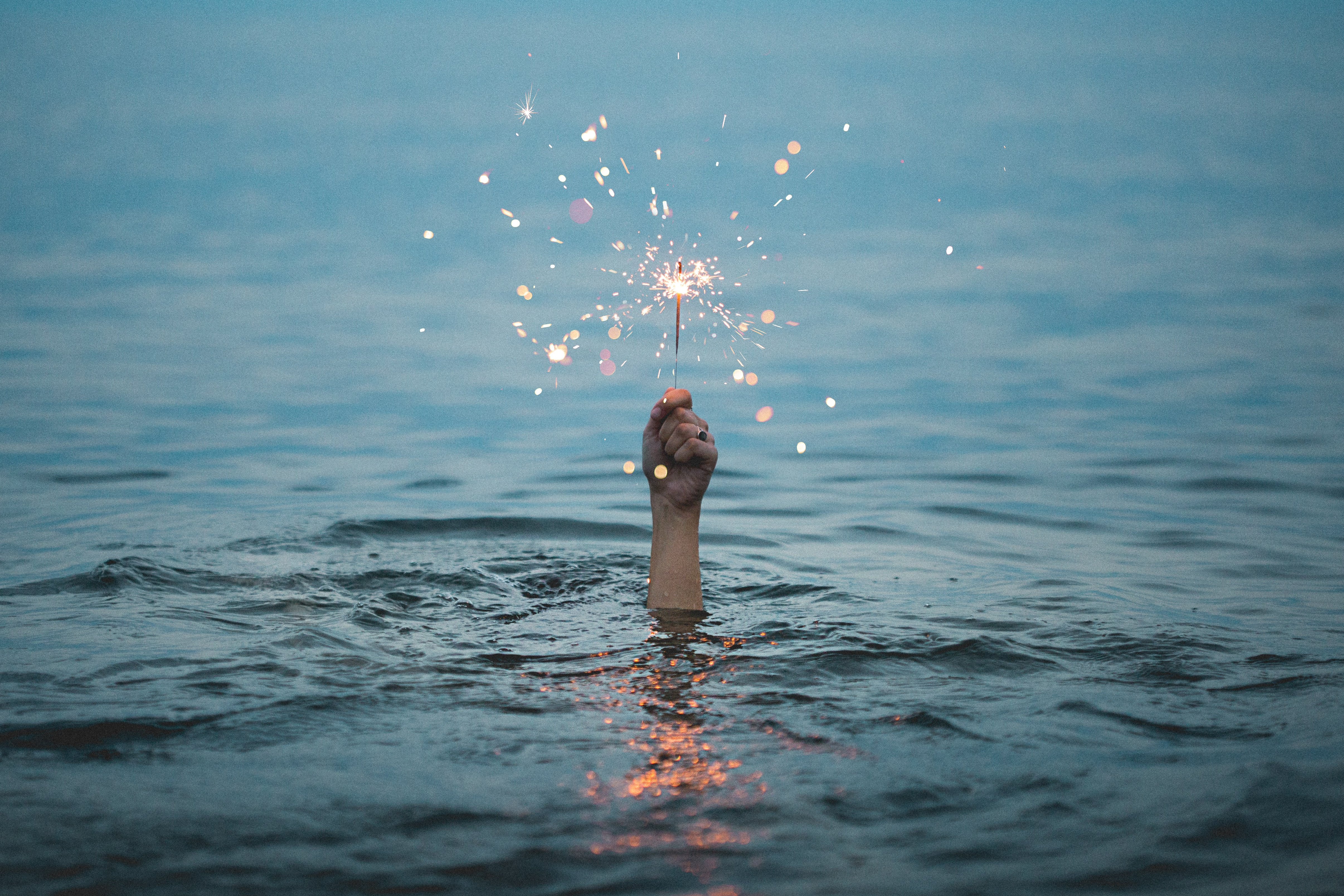 person submerged in body of water holding sparkler