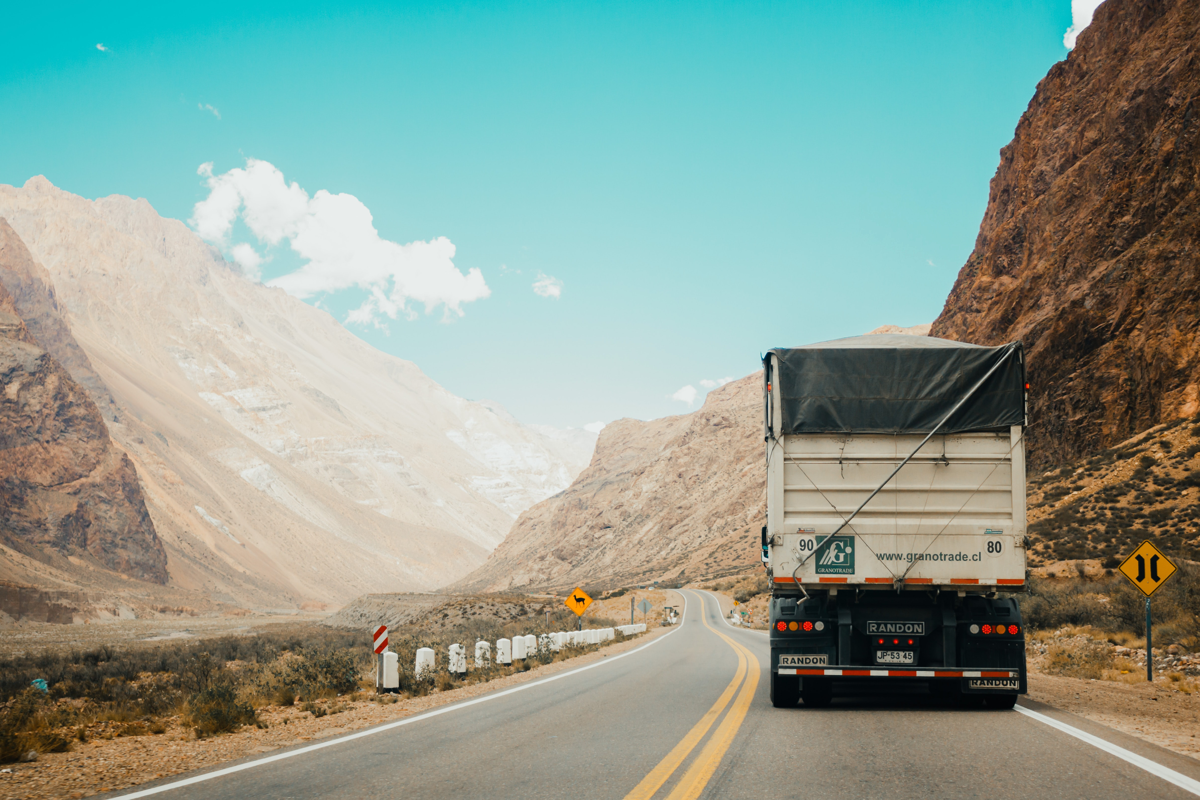 Truck driving on a road with blue sky in the background.